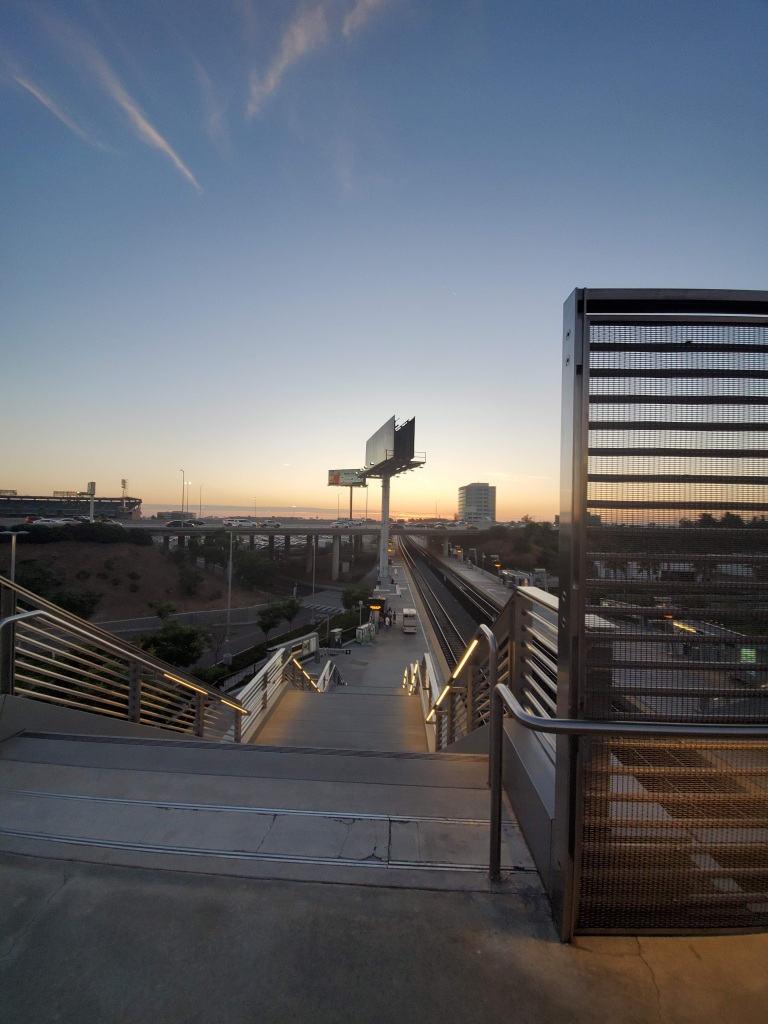 A stair case leading down to a train platform. The sun is setting on a highway.