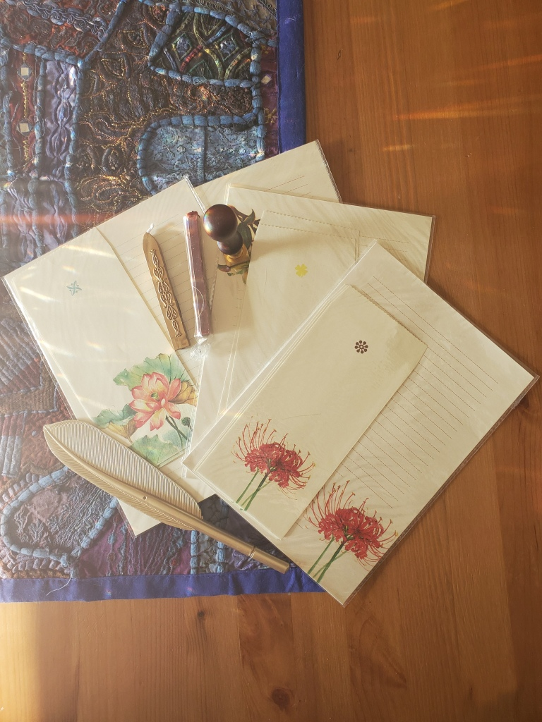 Image of floral paper, fancy plastic feather pen, wax, and a seal.